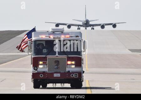 An American flag waves from the side of a fire truck with the Tinker Fire and Emergency Services section of the 72nd Civil Engineer Squadron while leading a KC-135R Stratotanker, serial # 58-0099, down a taxiway as the aircraft arrives for induction into periodic depot maintenance with the Oklahoma City Air Logistics Center, March 9, 2017, Tinker Air Force Base, Oklahoma. The 72nd CES operates four fire stations on Tinker AFB to provide around-the-clock protection to the massive base. - Stock Photo