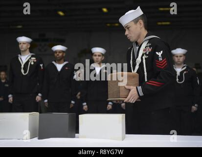 PACIFIC OCEAN (March 15, 2017) Boatswain's Mate 1st Class Harry Crawford carries cremains during a burial at sea board the aircraft carrier USS Nimitz (CVN 68). The ship committed 16 Sailors, one soldier and one civilian during the first burial-at-sea ceremony held on board in more than 2 years. Nimitz is underway to conduct composite training unit exercise in preparation for an upcoming deployment. - Stock Photo