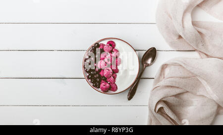 Raspberries and blueberries in a Bowl. Healthy breakfast concept with yoghurt and muesli - Stock Photo
