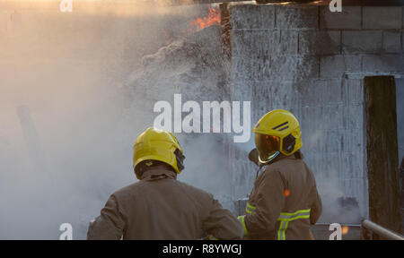 Fire fighters fighting a barn fire, Cumbria, UK - Stock Photo