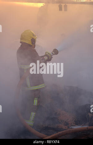 Fire crew tackling a farm fire with hay burning. Cumbria, UK. - Stock Photo