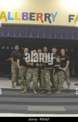 The 82nd Airborne Division rock band, Riser Burn, pictured from left to right: Spc. DGiovhani Denize, Spc. Chris Deroche, Sgt. 1st Class Kevin Quinones, Staff Sgt. Tony Buzzella, Spc. Andrews Santana, Staff Sgt. Traci Gregg, Sgt. Patrick O'Hara, Spc. Rachel Watson, Staff Sgt. Gunnar Kalstrom, after a concert for the children of Gallberry Farm Elementary School in Fayetteville, N.C., March 7, 2017, in honor of Music In Our Schools Month. The annual March celebration engages music educators, students and communities to promote the benefits of high quality music education programs in schools. - Stock Photo