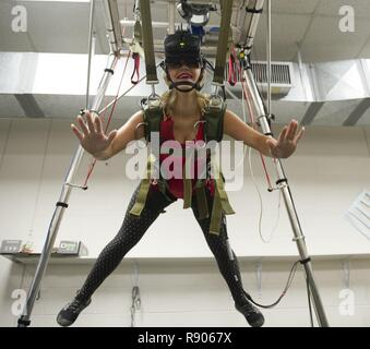 Demi, a Tampa Bay Buccaneers cheerleader, experiences freefall in the MC-60 parachute simulator at the parachute rigging facility while visiting MacDill Air Force Base in Tampa, Fla., Nov. 7, 2017. The cheerleaders toured U.S Special Operations Command and other base facilities to meet with service members and to get a glimpse of military life. - Stock Photo