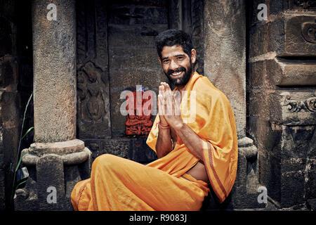 Naggar (Kullu Valley), North India - July 2013. Smiling Indian Brahmin. sitting near the temple of Lord Krishna. Hands folded in namaste mudra. - Stock Photo