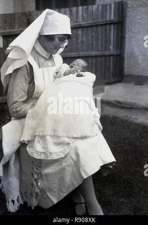 1920s, historical, a uniformed midwife sitting outside holding a small baby wrapped in a blanket on her lap. In Britain at this time, home births were the norm and some but not all new births would be looked after by experienced midwifes, who were formally trained, midwifery having been become legally recognised in 1902. After WW2 and the introduction of the NHS in 1946, women had access to Doctors (GPs) as well as midwives. - Stock Photo