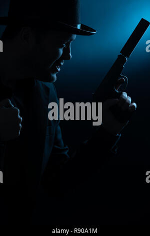 Image of side of man in black hat with pistol - Stock Photo