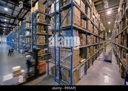 Overview of a large industrial distribution warehouse storing products in cardboard boxes on conveyor belts and racks. - Stock Photo