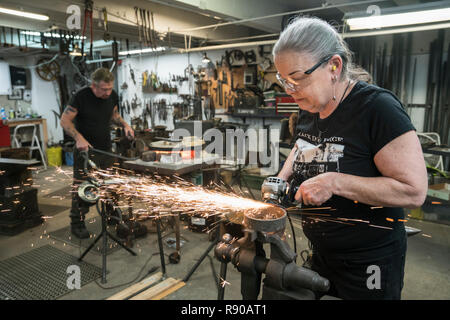 Caucasian female blacksmith grinding on a metal part in her studio.  Male blacksmith at work in the backround. - Stock Photo