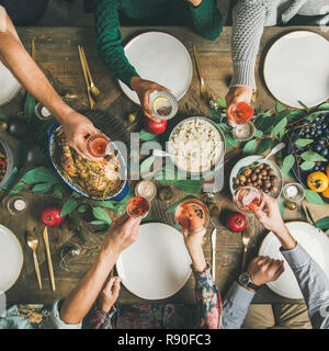 Traditional Christmas, New Year holiday celebration party. Flat-lay of friends or family feasting at festive table with turkey or chicken, vegetables, - Stock Photo