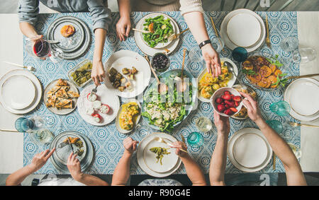 Mediterranean style dinner. Flat-lay of table with salads, starters, pastries over blue table cloth with hands holding drinks, sharing food, top view. - Stock Photo