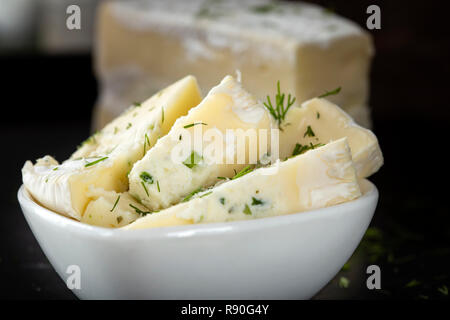 Pieces of brie cheese with cream and other herbs in a white bowl - close up view - Stock Photo