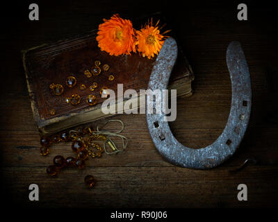 Broken. Still life, light painting, Old book, broken beads, dying flowers and worn out horseshoe. Metaphor for life, death. - Stock Photo