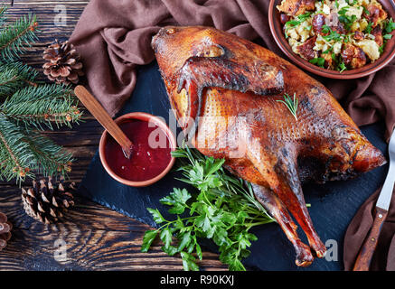 overhead view of delicious roast turkey served with cranberry sauce and dressing made with bread, celery, onions, apples, chestnuts and herbs. fir tre - Stock Photo