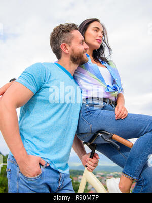 Why women more attracted biker guys. Girl sit on handlebar of his bike. Man bearded macho rides girlfriend on his bike. Idea for romantic date with bicycle. Girl likes he rides her on handlebar. - Stock Photo