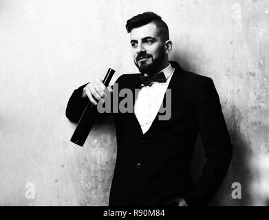 Man smiling and holding with bottle of wine in suit with red bow on background of beige color wall. Concept of party time and rest - Stock Photo