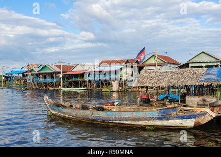 Old wooden boat and traditional houses on stilts in floating fishing village in Tonle Sap lake. Kampong Phluk, Siem Reap province, Cambodia, Asia - Stock Photo