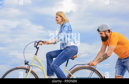 Support helps believe in yourself. Support and friendship. Woman rides bicycle sky background. Man helps keep balance ride bike. Girl cycling while man support her. Service and assistance. - Stock Photo