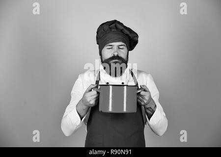 Man with beard holds kitchenware on blue background. Cook with dreamy face in burgundy hat and apron smells soup in pot. Cooking process concept. Chef with red casserole or saucepan - Stock Photo