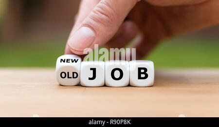Hand is turning a dice and changes the expression 'old job' to 'new job' - Stock Photo