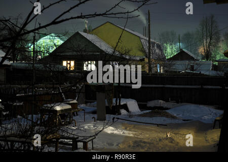 Kovrov, Russia. 24 January 2010. Courtyard of single storey old wooden house in the late evening - Stock Photo