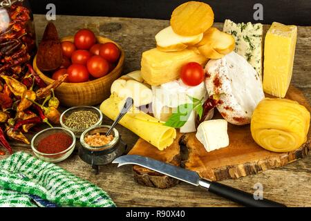 Various kinds of cheese served on wooden table. Wooden board with different kinds of delicious cheese on table. Sale of cheeses. Healthy food. Protein - Stock Photo