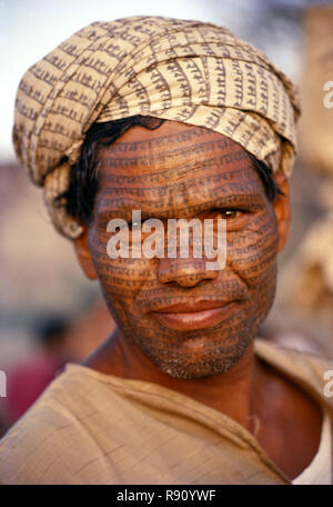 The tattooed face of a Ramnaami ascetic, with his hand painted cloth painted with the name of Lord Ram tied around his head like a turban - Stock Photo