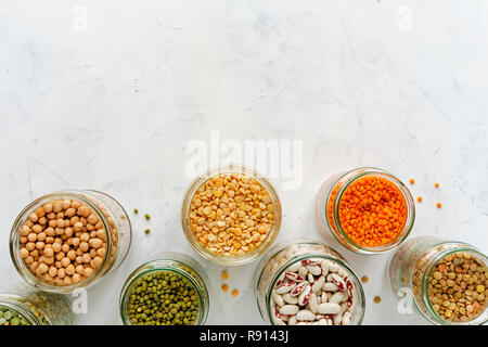 Open glass jars full of assorted dried legumes with mung beans, beans, lentils and peas over a white background in a healthy diet and nutrition concep - Stock Photo