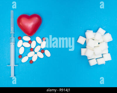 high level of sugar in blood cause heart disease. pills, drugs, red heart and syringe of injection and white blocks of refined sugar on blue backgroun - Stock Photo