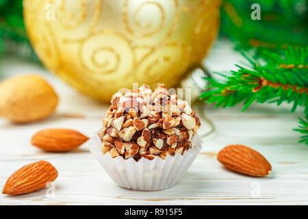 Homemade chocolate truffles with almonds on white wooden table with fir branches and festive toys balls. Gift for Christmas and New year. Gourmet. Sel - Stock Photo