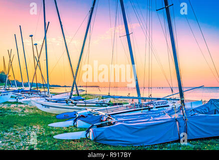 The sun rises over sailboats lined up along Front Beach at Ocean Springs Yacht Club, Aug. 26, 2014, in Ocean Springs, Mississippi. - Stock Photo