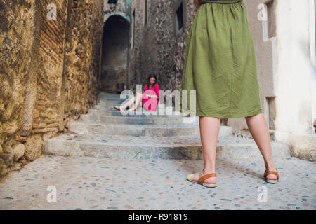 young tourist photographing her friend in the city. - Stock Photo