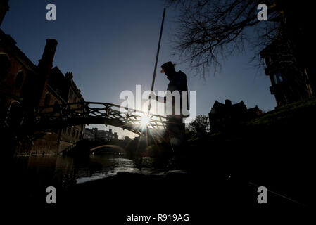 A punt chauffeur makes his way under the Mathematical Bridge at Queens College along the river Cam in Cambridge. - Stock Photo