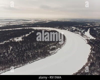 Aerial view of the snowy river and the shadows of the trees, after the winter. Abstract drawing created by nature in the snow with a drone. - Stock Photo