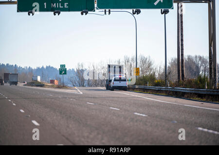 A patrol policeman on a truck with flashing lights stopped a big rig semi truck with flat bed semi trailer with commercial cargo at the exit from the  - Stock Photo