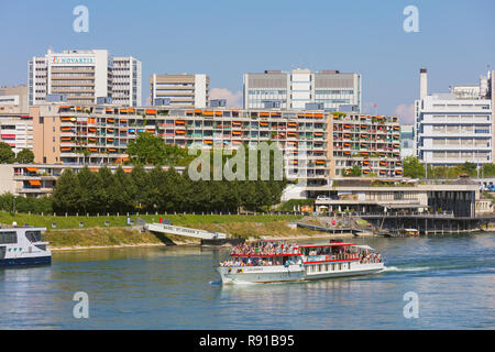 Buildings of the city of Basel, the Lallekonig boat with passengers on board passing along the Rhine river - Stock Photo
