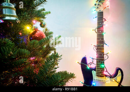 baeca991fb416 Seasonal holiday musical instrument electric guitar wrapped in Christmas  tree string lights - Stock Photo