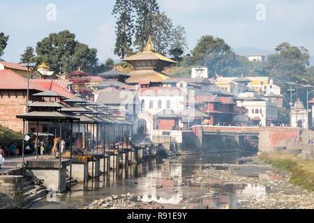 Cremation ghats on the Bagmati river at Pashupatinath, Nepal's most important Hindu temple, Kathmandu. - Stock Photo