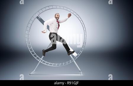caucasian businessman in hamster wheele is happy to work hard - Stock Photo