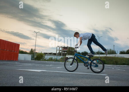 Teen boy riding bicycle standing on one leg - Stock Photo