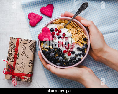 Festive and Healthy breakfast for loved ones. Cereal biscuits in pink glaze, cornflakes, yogurt, fresh berries on the background of white boards. Clos - Stock Photo