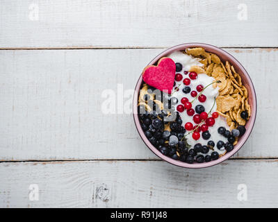 Healthy breakfast. Cereal biscuits in pink glaze, cornflakes, yogurt and fresh berries on the background of white boards. Close-up, top view, isolated - Stock Photo