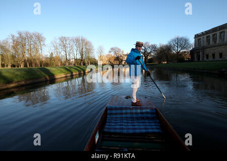 A punt chauffeur makes his way  along the river Cam in Cambridge. - Stock Photo