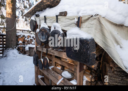 Old pans in burnt ash hanging on wall. A warm looking cottage at the middle of a snowy winter forest. Firewood stacked in piles, covered with snow. cutted trunks in a alpine hut in winter forest - Stock Photo