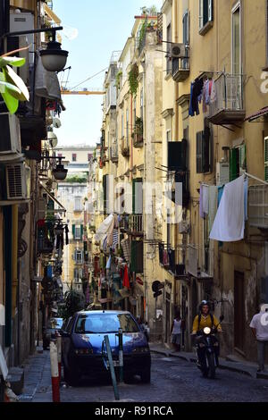 Narrow cobble stone paved streets with tall Mediterranean style apartment houses in center of Naples in Italy. - Stock Photo