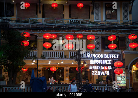 Nha Trang, Vietnam: Asian restaurant exterior decorated with red paper lanterns. People eating at a Chinese buffet, view of windows from outside - Stock Photo