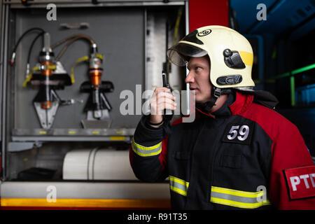 Image of male firefighter in helmet talking on walkie-talkie - Stock Photo