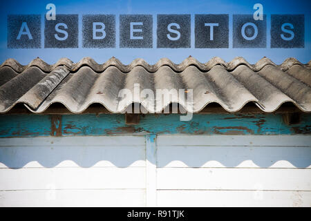 Dangerous asbestos roof.  The word asbestos written with letters whose graphic resembles the shape of the asbestos particles. - Stock Photo