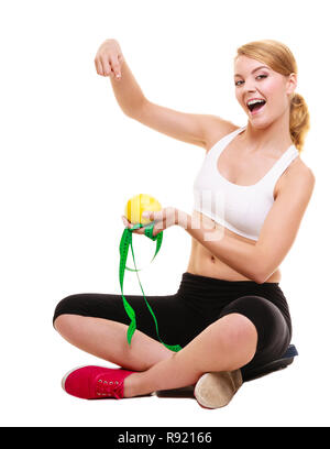 Joyful happy woman girl holds holding grapefruit and measurement tape points pointing and sitting. Fitness and healthy lifestyle concept. Dieting and  - Stock Photo