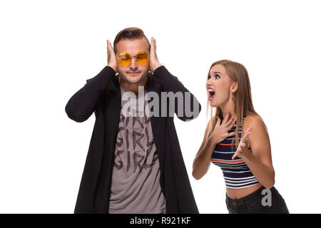Angry blonde young European woman gestures with hands, shouts at husband who is guilty, stands together against white background, have dispute and quarrel - Stock Photo