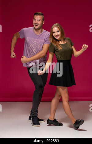 Funny young modern couple dancing and having fun together over burgundy background